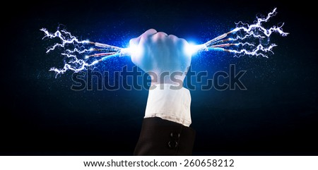 Business person holding electrical powered wires concept on background - stock photo
