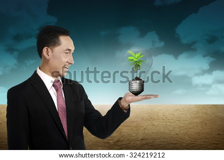 Business person holding light bulb with plant inside. Green energy concept