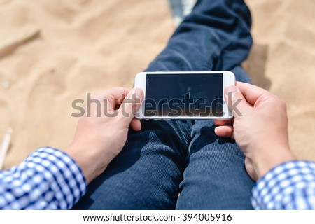 Business person holding smartphone on the outdoors beach background, top view closeup. Wireless 4g technology on travel vacation - stock photo