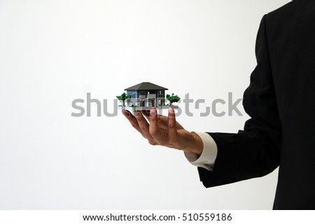 business person holds house miniature model