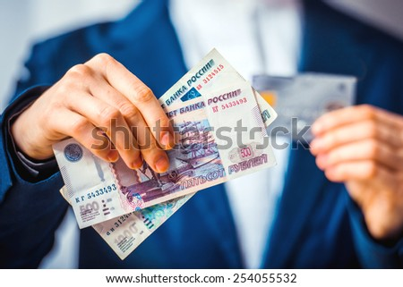 Business person holds russian roubles and plastic credit card - stock photo