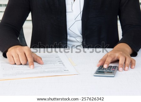 Business person in black suit working on financial accounts in office - stock photo