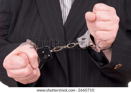 Business person in suit in handcuffs - stock photo