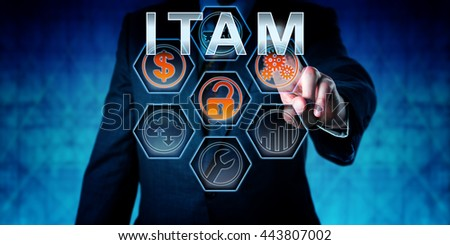 Business person is touching ITAM on an interactive virtual control monitor. Business strategic metaphor, information technology concept, corporate terminology and acronym for IT Asset Management. - stock photo