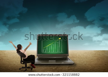 Business person looking giant laptop on the desert. Wireless concept - stock photo