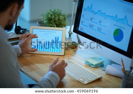 Business person using computer and digital tablet in his work