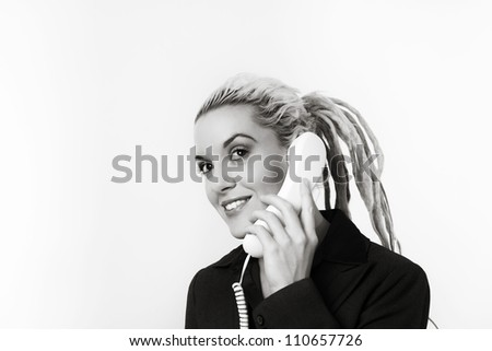 Business person with dreadlock hair on the phone at work looking very happy