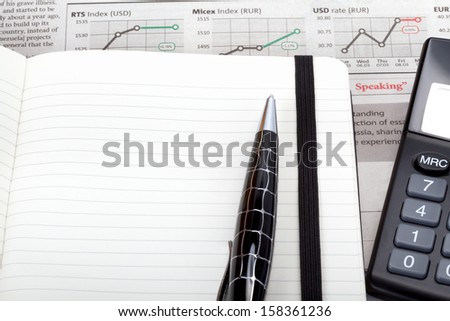 Business photo: open note with pen, calculator and newspaper (stock index overview) - stock photo