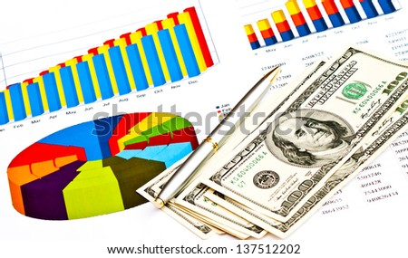 Business picture: money, pen and financial graphs  - stock photo