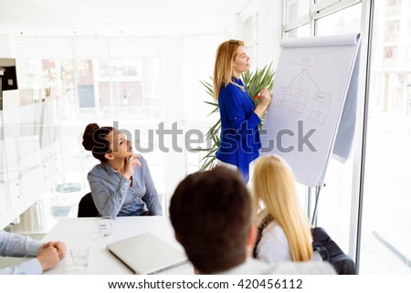 Business plan explained on flipchart by CEO to employees - stock photo