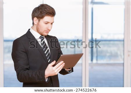 Business plan. Portrait of young businessman standing reflectively and holding the tablet
