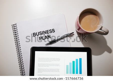 Business plan with touchscreen and coffee. - stock photo