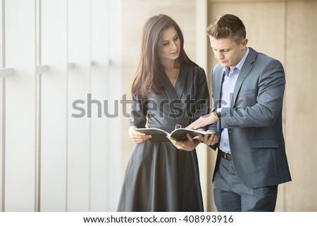 Business portrait of a girl and a guy in the interior of a modern business center with panoramic windows. Both are dressed in strict sofisnye costumes. Boss with interest the fact that he shows his - stock photo