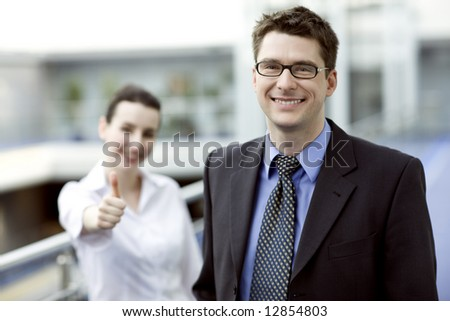 Business portrait - young handsom man with thumbs up sign in backgroud - stock photo