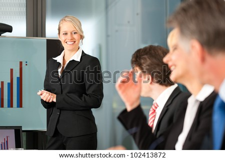 Business - presentation within a team, a female, colleague is standing on the flipchart - stock photo