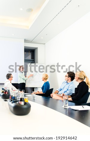 Business - presentation within a team, a female colleague is standing on the flipchart and explaining the development - stock photo