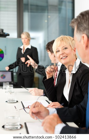 Business - presentation within a team, a female, colleague is standing on the flipchart, one woman is looking into the camera - stock photo