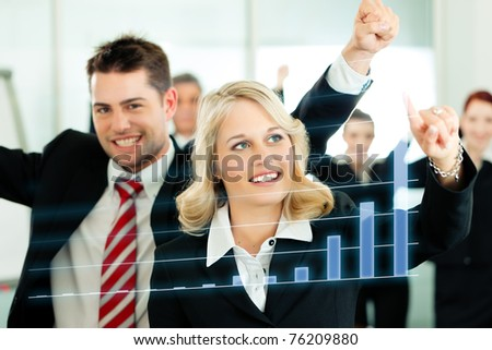 Business - presentation within a team; a female colleague shows graph or chart on screen - stock photo