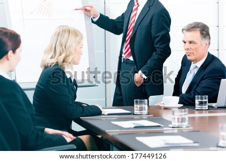 Business - presentation within a team in office, a colleague is standing on the flipchart