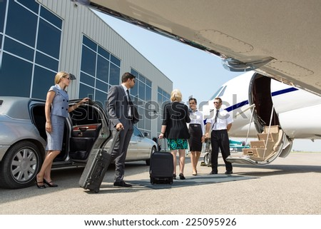 Business professional about to board private jet while airhostess and pilot greeting them - stock photo