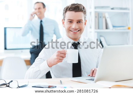 Business professional.Cheerful businessman in formalwear holding a cup of coffee and smiling at camera while sitting at his desk in office - stock photo