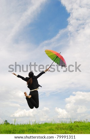 Business rainbow umbrella woman jumping to blue sky in grassland with rainbow umbrella - stock photo