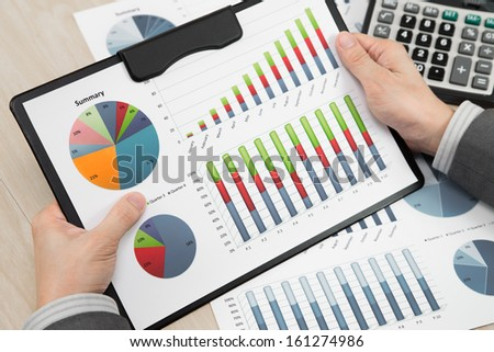 business report and man hand with pen - stock photo