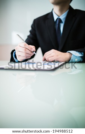 business report and man hand with pen. Accounting - stock photo
