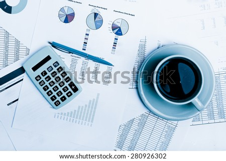 Business report. Cup of coffee on document. Accounting.  Blue toned - stock photo