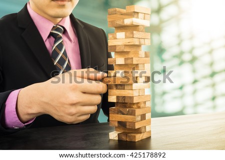 Business risk concept with wood jenga game.Businessman manage his strategy. - stock photo