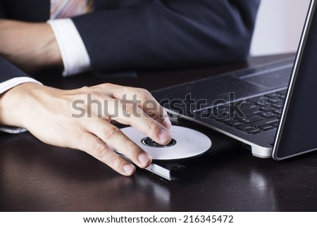 Business's hand holding Disk insert to laptop computer  - stock photo