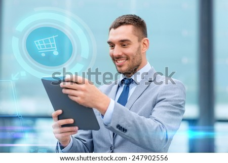 business, sale, technology and people concept - smiling businessman with tablet pc computer and virtual shopping trolley icon hologram on city street - stock photo