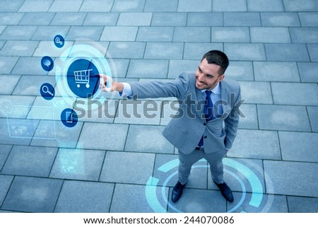 business, sale, technology and people concept - young smiling businessman pointing finger to shopping trolley icon on virtual screen outdoors from top - stock photo