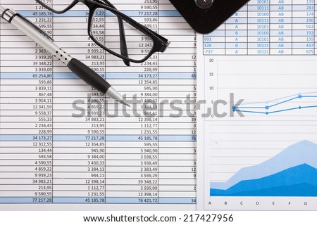 Business scene: calculator, pen and eyeglasses over business documents - stock photo