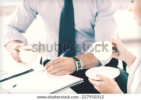 business, school and education concept - smiling businesswoman and businessman discussing something in office - stock photo