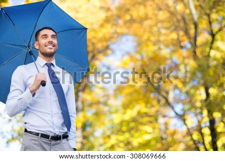 business, season, weather and people and concept - young smiling businessman with umbrella over autumn natural background - stock photo