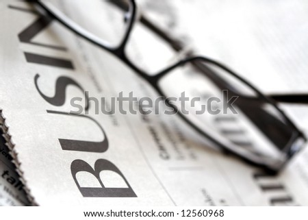 Business Section of Newspaper with Reading Glasses