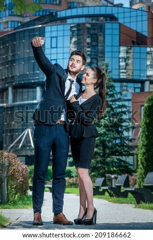 Business Selfie. Portrait of two confident and successful businessmen. Business couple standing embracing and holding mobile phone. - stock photo