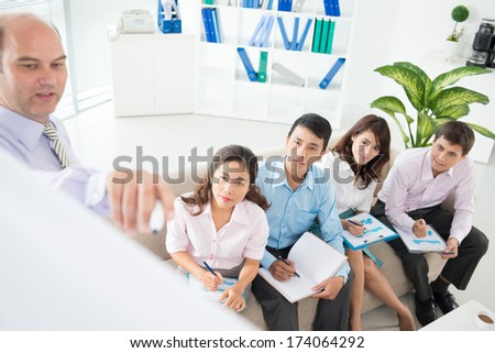 Business seminar where a boss explaining the company strategy to his colleagues, they listening to him with attention on the foreground  - stock photo