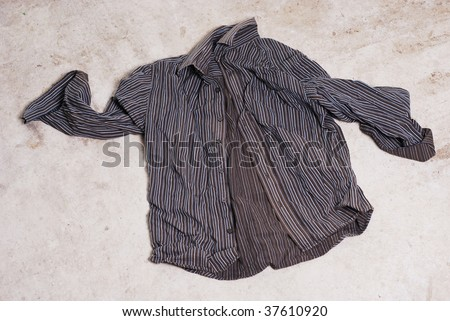 Business shirt crumpled and abandoned on an old concrete floor. Freedom or unemployment? - stock photo