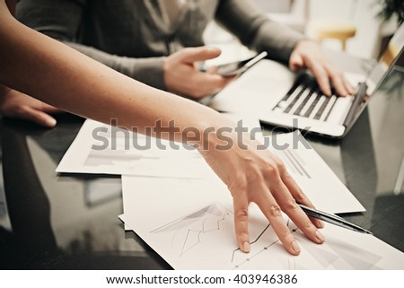 Business situation,team work,brainstorming. Photo female hand holding pen. Man using smartphone and modern laptop. Working process office. Discussion startup. Horizontal.Blurred,film effect - stock photo