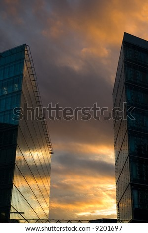 Business skyscrapers with windows fully made of glass mirroring sky and clouds, other skyscrapers and buildings.