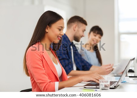 business, startup, education and people concept - happy young african woman typing on laptop computer over creative team or students working at office - stock photo