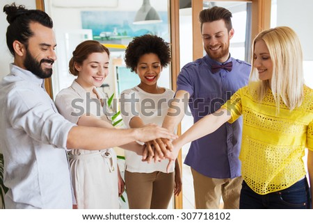 business, startup, gesture, people and teamwork concept - happy creative team with hands on top of each other in office - stock photo