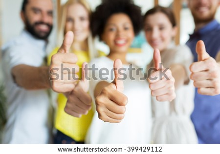 business, startup, people, gesture and teamwork concept - close up of happy smiling creative team showing thumbs up in office - stock photo