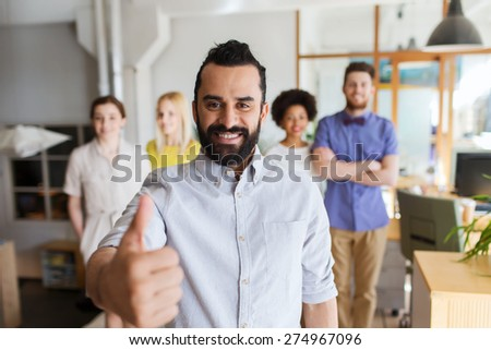 business, startup, people, success and teamwork concept - happy young man with beard over creative team showing thumbs up in office - stock photo