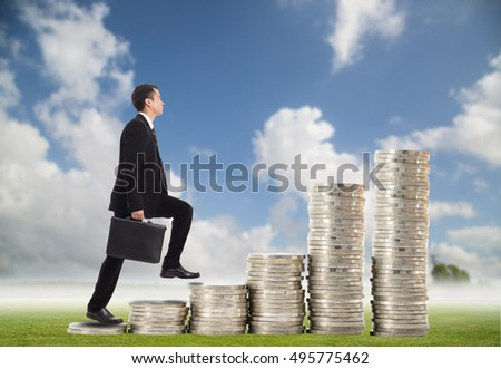 Business step up.Businessman walk on stack coins which growing success and investment with his money.