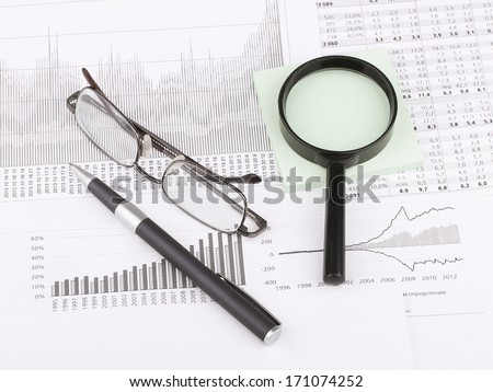 Business still-life: graph, table, eyeglasses, magnifier, green sticky, blue pen