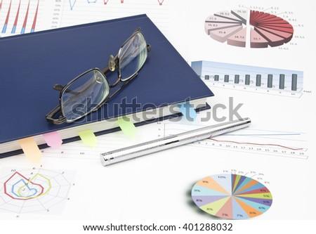 Business still-life of a charts, eyeglasses, shiny pen, diary - stock photo