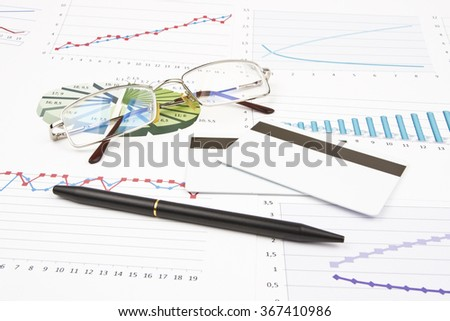 Business still-life of a credit card, black pen, eyeglasses, charts